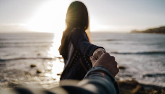 moça segurando a mão do rapaz na praia