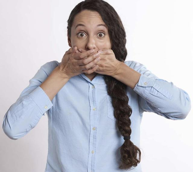 mulher com os olhos arregalados e as mãos sobre a boca
